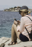 Woman in cap and with backpack is seating near of the sea Stock Images