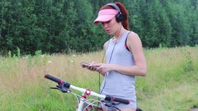 Woman in cap with bicycle listens to music at summer stock video footage
