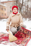 Woman in  cap cleans carpet with snow Royalty Free Stock Photos