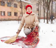Woman in cap cleans carpet with snow Royalty Free Stock Photography