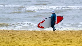 A woman with a cap on the head, practicing stand up paddle, on the North Sea in the Netherlands with large waves and strong winds royalty free stock photo