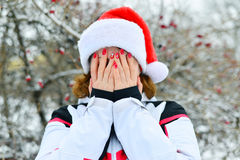 Woman in cap Santa Claus covers her face with her hands Stock Photo