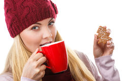Woman in cap and shawl holding gingerbread and cup of hot tea, christmas time Royalty Free Stock Photo