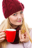 Woman in cap and shawl holding gingerbread and cup of hot tea, christmas time Stock Photos
