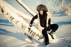Woman in a cap on their haunches of the birch Stock Photography