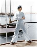 Woman in a captains hat standing on top of a sailboat Stock Photo