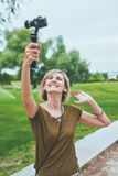 Woman capturing herself with personal camera Stock Images