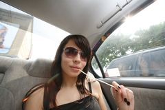Woman in car. Young brunette woman in sunglasses in car Royalty Free Stock Photo