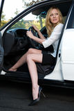 Woman in car. Pretty blond woman in white blouse and black skirt sitting in a white car with one leg out about to get out stock photography