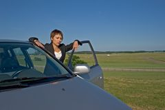 Woman in the car. Young woman with a modern car of gray color Stock Photography