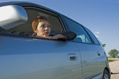 Woman in the car. Young woman with a modern car of gray color Royalty Free Stock Image