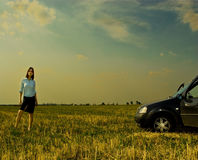 Woman and car. Young woman and car in a field Stock Image