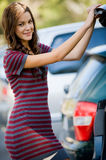 Woman By Car. A young female student standing at the rear of a car Royalty Free Stock Images