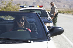 Woman In Car Being Pulled Over By Police Officer. View of an Asian woman sitting in car being pulled over by police officer on desert road Royalty Free Stock Photos