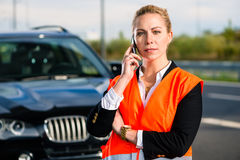 Woman with car breakdown calling towing company. With phone Royalty Free Stock Photo