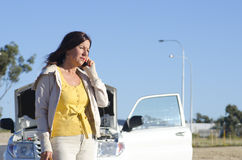 Woman car breakdown road assistance. Stressed mature woman breakdown with car on remote road calling for assistance, for help on mobile phone, isolated with blue Royalty Free Stock Photos