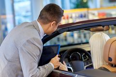 Woman and car dealer with tablet pc in auto salon Royalty Free Stock Photos