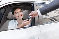 Woman at car dealership, buying new auto. Car dealership. Woman buying new auto, salesman giving her the key stock image