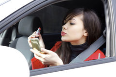 Woman in a car doing makeup. Royalty Free Stock Photos
