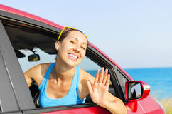 Woman car driver happy. Beautiful girl in a car smiling on a background of blue sea Royalty Free Stock Images
