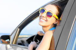 Woman car driver happy. Beautiful girl in a car smiling on a background of blue sea Stock Photo