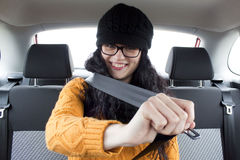 Woman in a car fasting her seat belt. Smiling Royalty Free Stock Photos