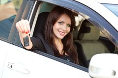 Woman in car holding key Stock Photos