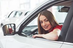 Woman in car indoor keeps wheel turning around smiling looking at passengers in back seat idea taxi driver against Royalty Free Stock Images