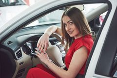 Woman in car indoor keeps wheel turning around smiling looking at passengers in back seat idea taxi driver against Royalty Free Stock Photo