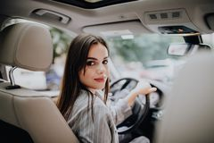 Woman in car indoor keeps wheel turning around smiling looking at passengers in back seat idea taxi driver talking to companion wh. Woman in car indoor keeps royalty free stock photography