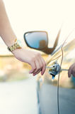Woman with car key. Opening car door. Woman´s hand unlocking a door on a car. Sunlight. Transportation. Stock Image