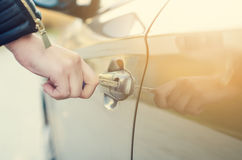 Woman with car key. Opening car door. Woman´s hand unlocking a door on a car. Sunlight. Transportation. Woman with car key. Opening car door. Woman´s hand Stock Photography