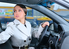 Woman in a car is looking backwards Royalty Free Stock Images