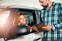 Woman in the car looking at car rental agreement and talking on stock photos