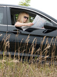 Woman in Car Looking at Map Royalty Free Stock Photos
