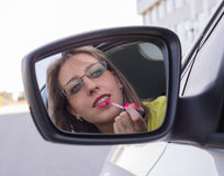 Woman in  car, looking at mirror and painting her lips Stock Photos