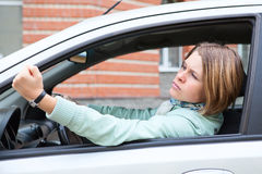 Woman in car making some bad gestures. Young woman in car making some bad gestures royalty free stock image