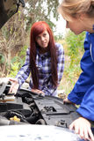 Woman car mechanic repairs engine damaged car Stock Image