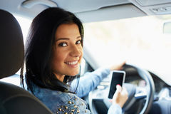 Woman in the car with mobile phone royalty free stock photography