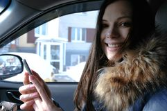 Woman in a car with a mobile phone. Young beautiful brunette woman looking at camera. Woman in a car with a mobile phone. Young beautiful brunette woman looking stock photos