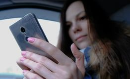 Woman in a car with a mobile phone. Young beautiful brunette woman looking something in the mobile phone. Woman in a car with a mobile phone. Young beautiful royalty free stock photo