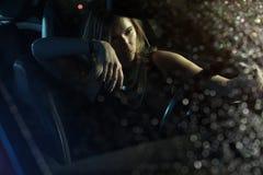 Woman in car night light. Sit rain stock image