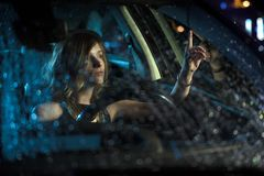 Woman in car night light. Sit rain stock photography