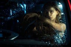 Woman in car night light. Sit rain stock photo