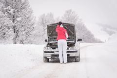Woman with car probelm in winter mountain road stock photo