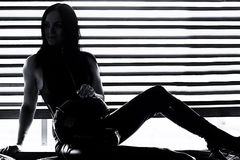Woman car racer in leather suit holding a helmet. Black and whit Stock Photo
