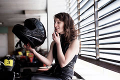 Woman car racer in leather suit holding a helmet and do make up Royalty Free Stock Images