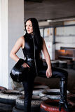 Woman car racer in leather suit holding a helmet Stock Photography