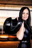Woman car racer in leather suit holding a helmet Stock Photos