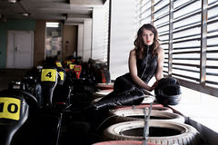 Woman car racer in leather suit holding a helmet Stock Images